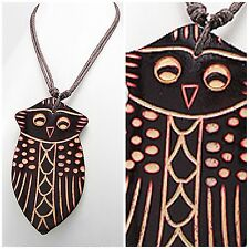 Cotton necklace with carved wood centerpiece depicting owl patterns.
