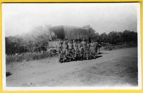 1943 PC Named soldiers standing by a lorry in Olive Grove Nr. Sousse, Tunisia.