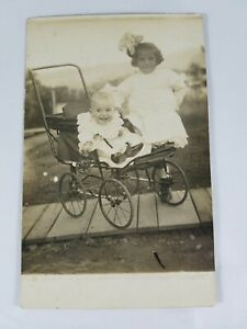 Vintage-Real-Photo-Post-Card-Smiling-Baby-in-Stroller-amp-Girl-w-Bow-AZO-1910-039-s
