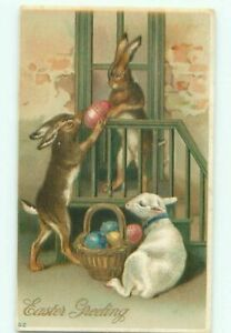 Easter-Postcard-HUMANIZED-BUNNY-RABBITS-PASSING-EGGS-DOWN-FROM-PORCH-w-LAMB-b547