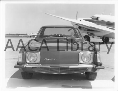 Ref. # 25554 Factory Photograph 1964 Studebaker Avanti in front of plane