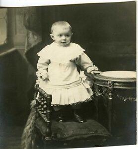 CARTE-PHOTO-portrait-un-bebe-baby-debout-sur-un-siege-fashion-mode-circa-1900