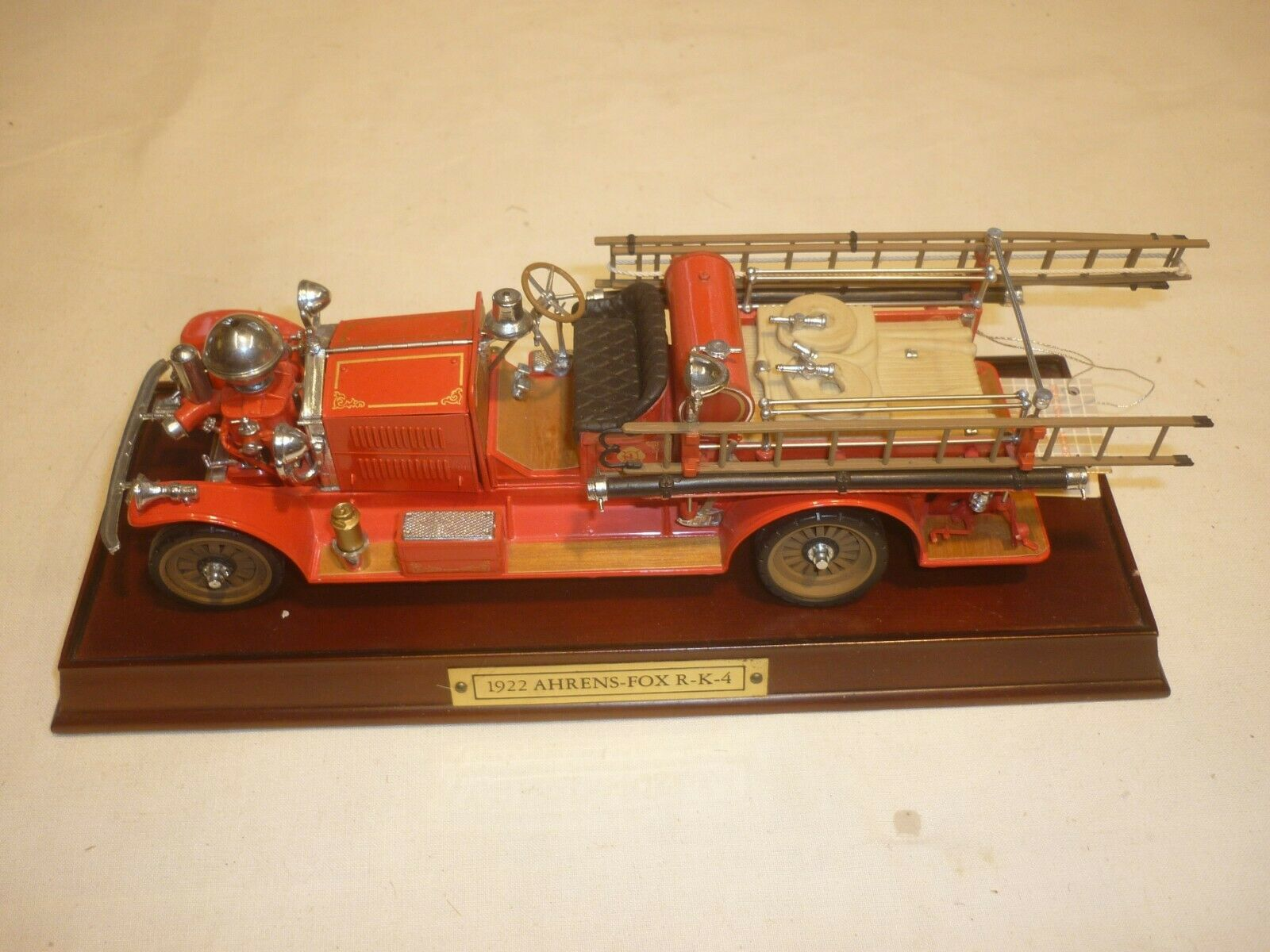 A Franklin mint of a scale model of a 1922 Ahrens Fire engine on wooden base