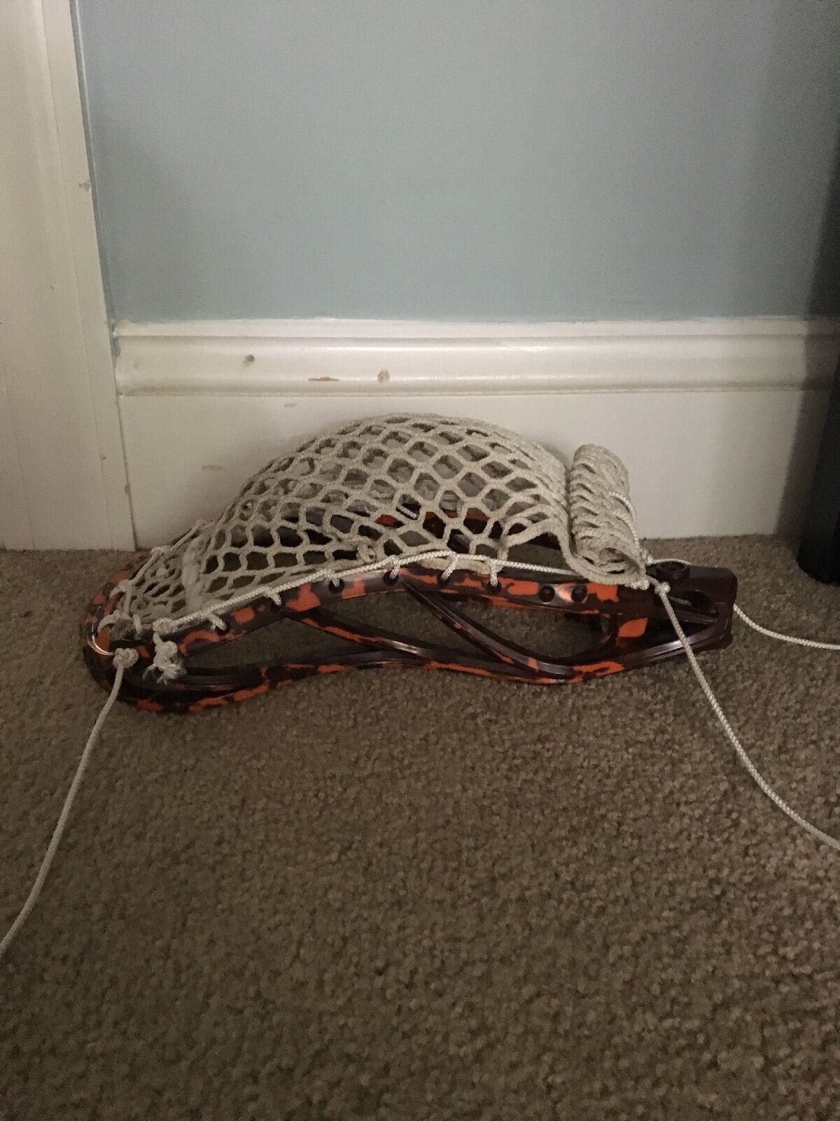 Lacrosse head strung and dyed with a orange maroon color