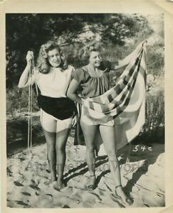 Two-women-undressing-on-beach-vintage-pinup-photo