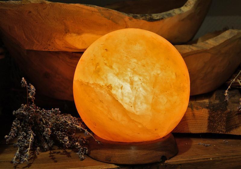 Die edle Lampe aus Salzkristall in Kugelform mit Holzfuß und Leuchtmittel