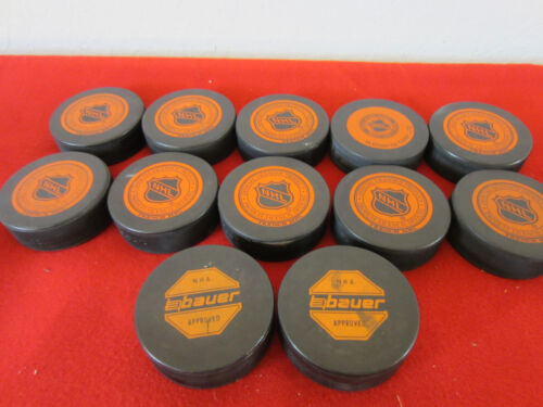 COLLECTION OF 10 N.H.L.& 2 N.H.A. OFFICIAL HOCKEY PUCKS