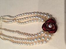 Triple strand pearl necklace with 14K yellow gold clasp with enamel flower