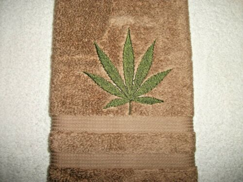 MARIJUANA LEAF DESIGN EMBROIDERED ONTO A TAN COLOR HAND TOWEL
