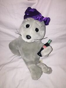 Coca Cola Advertising Seal  1998  Purple Cap Holding A Bottle Of Coca Cola - <span itemprop='availableAtOrFrom'>Stoke on Trent, Staffordshire, United Kingdom</span> - Coca Cola Advertising Seal  1998  Purple Cap Holding A Bottle Of Coca Cola - Stoke on Trent, Staffordshire, United Kingdom