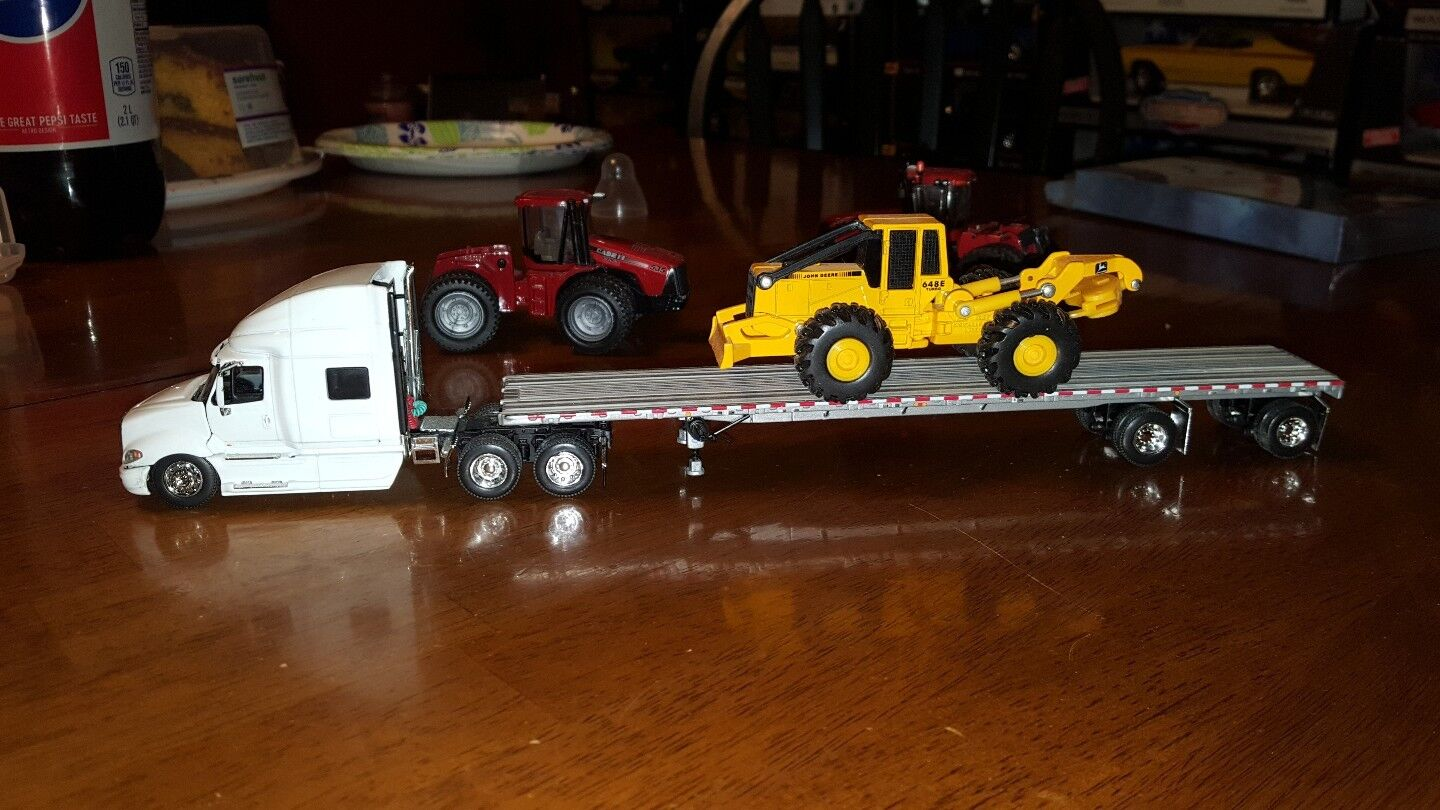 DCP 1 64 SCALE INTERNATIONAL PROSTAR with FLAT TRAILER AND HEAVY EQUIPMENT
