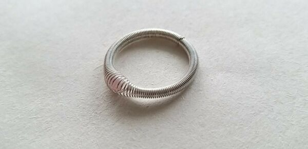 Silver coloured stackable stretch expanding ring with pink coloured bead