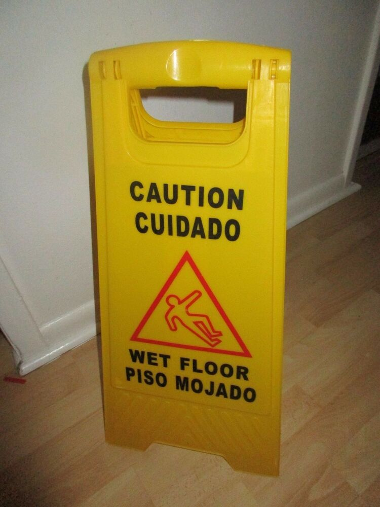 Yellow caution wet floor sign in english and in spanish for Floor in spanish