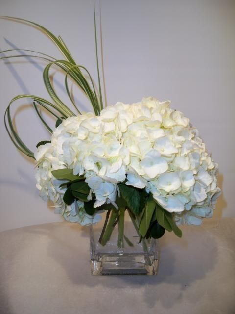 Artificial white hydrangea flowers arranged in glass cube