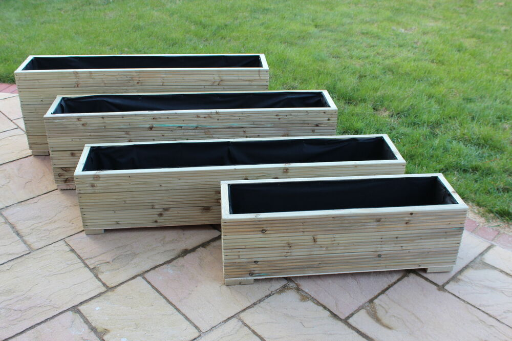 Large wooden garden planter trough in decking boards plant