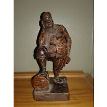 Vintage wood carving man resting on log