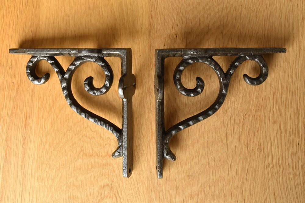 A PAIR OF ANTIQUE STYLE SMALL HAMMERED IRON BRACKETS CAST