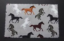 Un metro in popeline di cotone con cavalli in bianco, marrone, grigio, nero su grigio chiaro