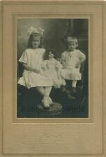 Cute children posing with toy doll antique cabinet photo