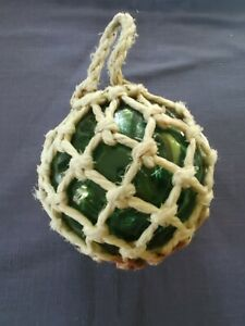 green glass fishing float wrapped with rope