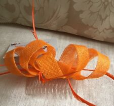 Orange loop fascinator with biot feathers on a comb. Gorgeous on!
