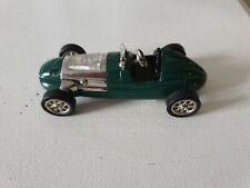 Vintage diecast racing car with clock on bonnet.