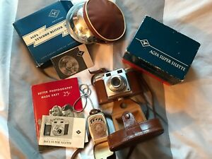 vintage camera, flash, and light meter with filters and cases and instructions