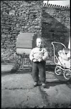 Small format negative - Young child - with pram and push-chair in background.