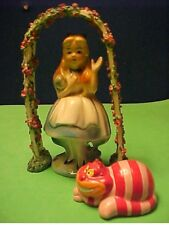 Ceramic figurine of Alice In Wonderland under trellis with cat