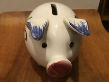 A hand painted ceramic piggy bank with floral decoration.