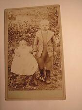 2 Kinder - stehender Junge & Baby auf einem Kinderstuhl im Garten / CDV