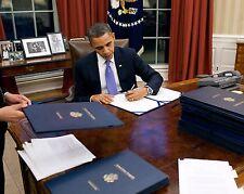 PRESIDENT BARACK OBAMA SIGNS LEGISLATION IN THE OVAL OFFICE  8X10 PHOTO (ZY-376)