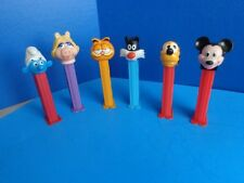 GROUP OF 7 VINTAGE PEZ CONTAINERS- CARTOON CHARACTER THEME- SMURF, SNOOPY,ETC