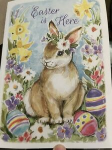 """""""Easter is Here"""" Card- With Cute Cartoon Bunny in flowery field with Easter Eggs"""