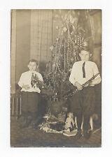 1910 BROWNIE SOUVENIR RPPC, CHRISTMAS, BOYS W/ GERMAN WINDUP TOY CAROUSEL, DOLL