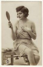 PORTRAIT OF A PRETTY SEMI NUDE WOMAN ADMIRING SELF IN THE MIRROR