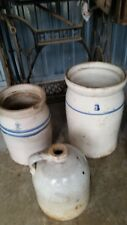 2 antique butter churns and a whiskey jug