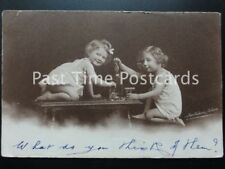 c1905 - showing two small children playing with Alcohol & old soda water bottle