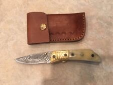 Damascus folding blade knife w/white bone handle, etched brass & leather case