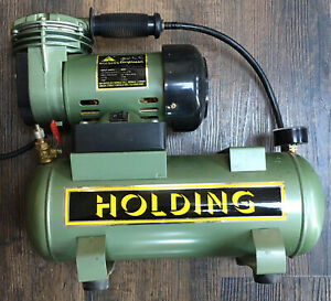 Holding Ripmax Mini Air Compressor With Gauge and Storage Tank 32psi