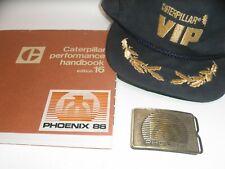 VINTAGE CATERPILLAR  1986 PROVING GROUND BELT BUCKLE, CAT 16 HANDBOOK, VIP CAP