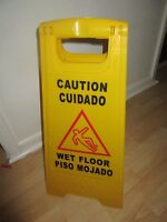 Yellow caution Wet Floor sign in English and in Spanish#