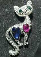 Silver tone cat brooch posing with blue/pink stones & emrald green coloured eyes