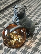 Vintage solid metal black pug dog statue with amber colored glass globe.
