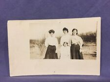 Three women and girl in front of fence real photo postcard