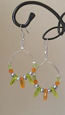 Handmade orange, green and silver coloured beaded dangly earrings .