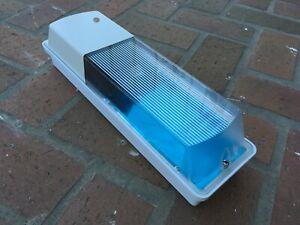 A DUSK TO DAWN WALL SECURITY LIGHT FIXTURE WITH 65 WATT FLUORECENT LIGHT BULB