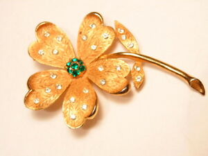 Gold colored floral fashion pin by JJ;  green center stone and crystal accents