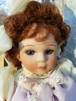 "porcelain 9"" tall Vintage doll with auburn curly hair and blue eyes"