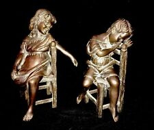 Bronze Statues Of A Boy & Girl Sitting On Chairs